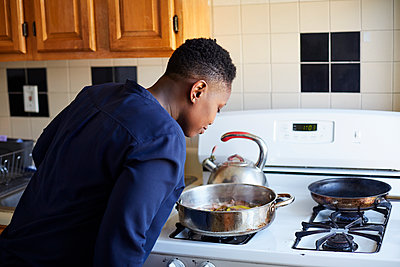 Black woman smelling food cooking in pan on stove - p555m1231809 by Granger Wootz