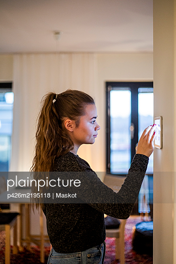Teenage girl using digital tablet mounted on wall in smart home - p426m2195118 by Maskot