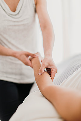 A massage therapist applies to pressure to her client's forearm - p1166m2107019 by Cavan Images