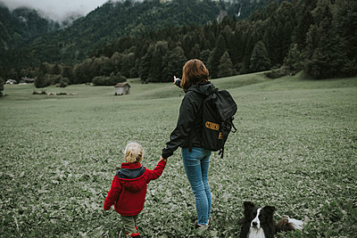 Austria, Vorarlberg, Mellau, mother and toddler with dog on a trip in the mountains - p300m2029168 by Frederik Franz