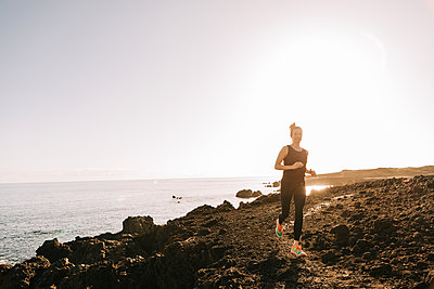 Young woman jogging on the beach - p713m2289610 by Florian Kresse