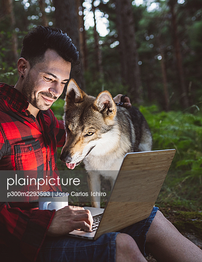 Male hiker with coffee cup using laptop while sitting by dog in forest - p300m2293593 by Jose Carlos Ichiro