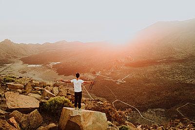 Man standing on rock watching sunset at caldera of Ca̱adas del Teide - p1166m2129924 by Cavan Images