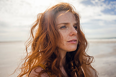 Portrait of a redheaded woman on the beach - p300m2023873 by Kniel Synnatzschke