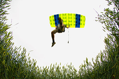 Person with parachute falling, low angle view - p31226178 by Hans Berggren