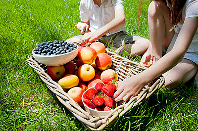 Cropped view of brother and sisters eating fruit from basket on grass - p429m943105f by Magdalena Niemczyk - ElanArt