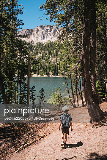 Rear view of boy walking through forest near Lake Mary, Mammoth Lakes, California, USA. - p924m2208578 by JFCreatives