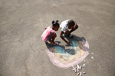 Brother and sister drawing rainbow with sidewalk chalk on pavement - p1023m2238483 by Himalayan Pics