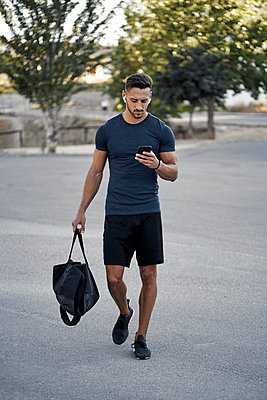 An athletic young man walking with a mobile phone in his hand - p1166m2212913 by Cavan Images
