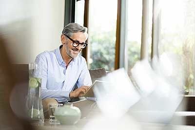 Man sitting in living room using tablet - p300m1175889 by Steve Brookland
