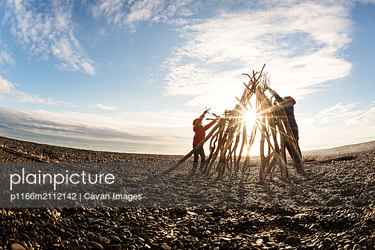 Two kids working together to build with driftwood at a beach - p1166m2112142 by Cavan Images