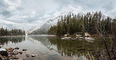 Scenic view of String Lake by trees against cloudy sky at Grand Teton National Park during winter - p1166m1571094 by Cavan Social