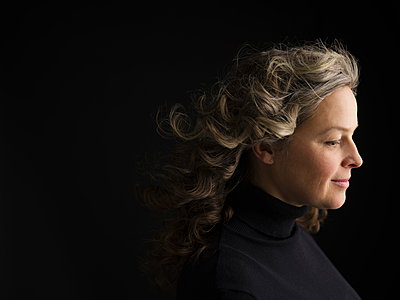 Profile portrait serene woman with curly gray hair looking down against black background - p1192m1403616 by Hero Images