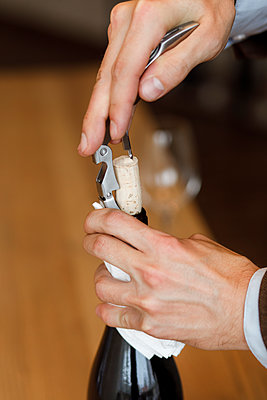 Hands of man opening bottle of wine - p1427m2110155 by Mykhailo Lukashuk