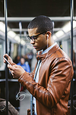 Portrait of businessman with smartphone and earphones hearing music on the subway train - p300m1019064f by Bonninstudio