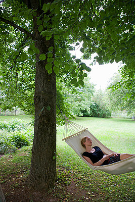 Woman relaxing in hammock - p42918292f by Christine Schneider