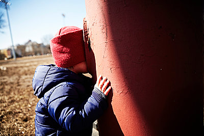 Male toddler playing hide and seek in park - p924m975876f by JPM