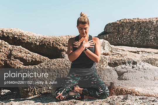 Young woman practises meditation on the beach - p1640m2261152 by Holly & John
