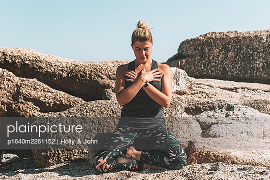 Junge Frau meditiert auf dem Strand - p1640m2261152 von Holly & John