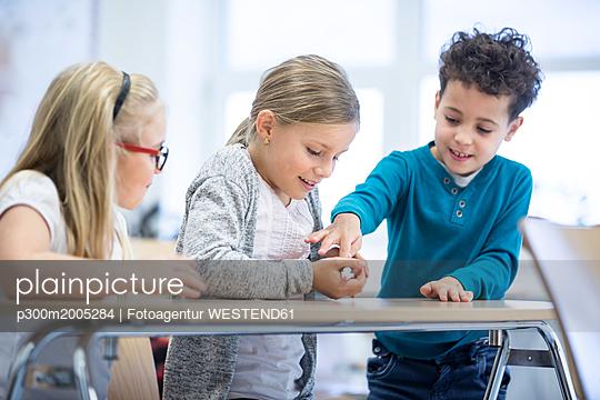 Three pupils in class stroking mouse - p300m2005284 von Fotoagentur WESTEND61