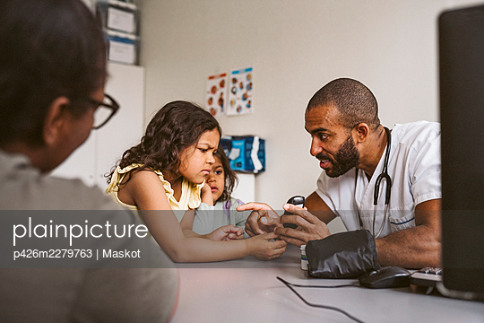 Male doctor showing glaucometer to girl in medical clinic - p426m2279763 by Maskot