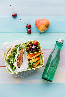 Healthy school food in a lunch box, vegetarian sandwich with cheese, lettuce, cucumber, egg and cress, sliced carrot and celery, cherries and pear - p300m2023803 by Ina Peters