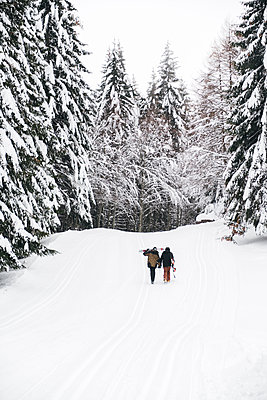 Italy, Modena, Cimone, rear view of couple with skiers and snowboard walking in winter forest - p300m2029359 von Juri Pozzi