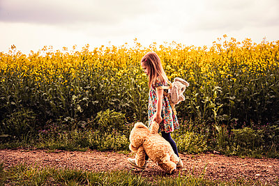Girl walking alone with teddy and backpack on a field way - p300m2103630 by Sebastian Dorn