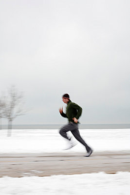 Young man running outdoors in winter - p3722617 by Grain Belt Pictures