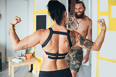 Bearded tattooed man with long brunette hair and woman with long brown hair showing her muscles standing indoors. - p429m2201701 by Eugenio Marongiu