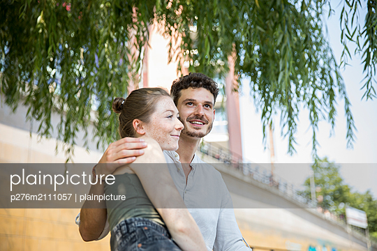 Young couple is resting in the shade of the tree - p276m2111057 by plainpicture