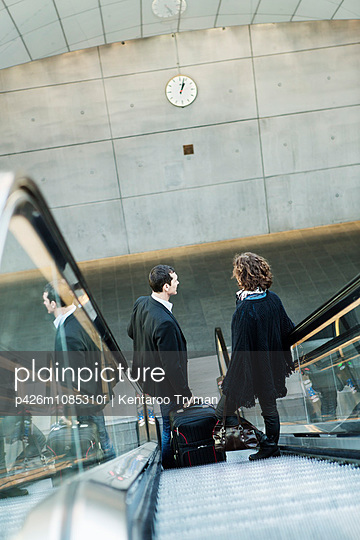 High angle view of business people moving down escalator in railway station - p426m1085310f by Kentaroo Tryman