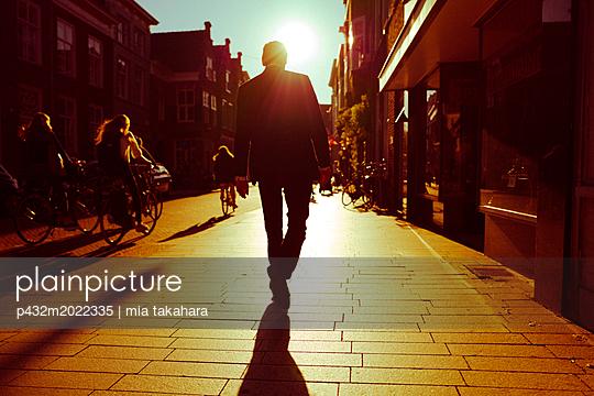 Männliche Silhouette auf Gehweg - p432m2022335 von mia takahara