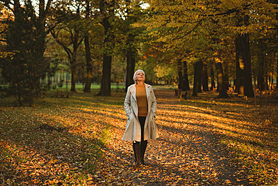 Thoughtful senior woman in jacket looking up in the autumn forest during daytime - p1315m1565665 by Wavebreak