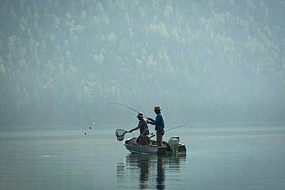 Two fishermen fishing in the river - p1315m2055874 by Wavebreak