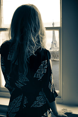 Back of young woman wearing 1980s dress, looking out of a window onto the Eiffel Tower. - p1433m1563445 by Wolf Kettler