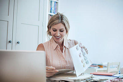 Smiling woman with laptop working on fashion designs on table - p300m2139646 by LOUIS CHRISTIAN