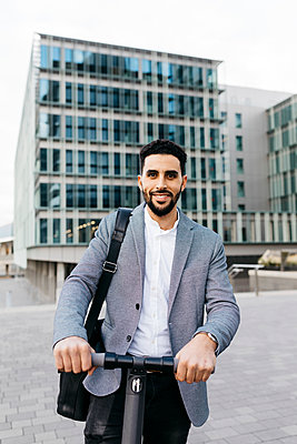Portrait of casual young businessman with electric scooter in the city - p300m2160571 by Josep Rovirosa