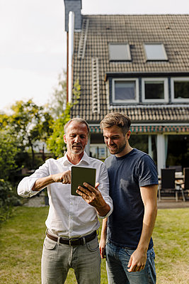 Father using digital tablet while standing by son in backyard - p300m2275089 by Gustafsson