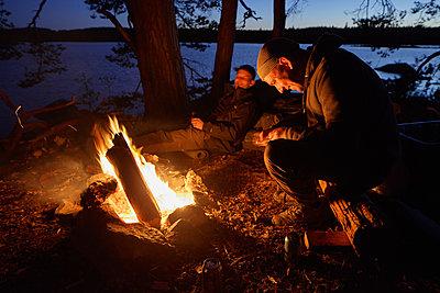 Sweden, Skane, Filkesjon, Mid adult men sitting around campfire at dusk - p352m1349333 by Gustaf Emanuelsson