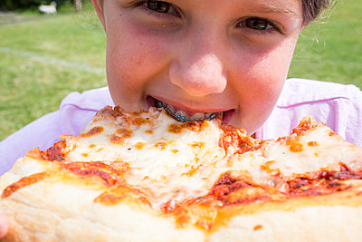 Close up of Caucasian girl with braces biting pizza - p555m1532422 by Adam Hester