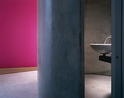 Modern cloakroom in a polished concrete drum adjacent to hall with pink walls. - p8551845 by Richard Bryant