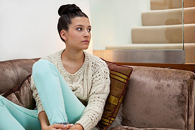 Pensive young woman on sofa - p924m711144f by Franek Strzeszewski
