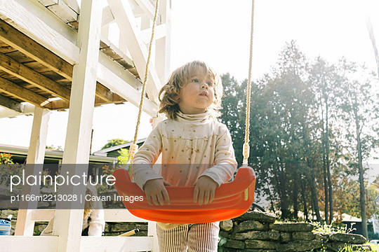 Little toddler girl holding on to her swing and looking away - p1166m2213028 by Cavan Images