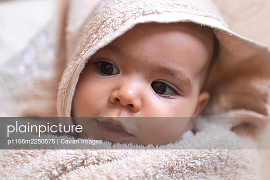 A beautiful baby rolled in a towel looking around in the bath - p1166m2250575 by Cavan Images