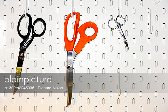 Three pairs of scissors hanging on a white pegboard - p1302m2245038 by Richard Nixon