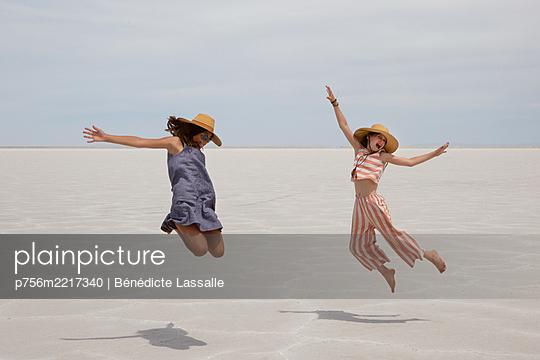 Zwei Mädchen machen Luftsprung in der Wüste - p756m2217340 von Bénédicte Lassalle