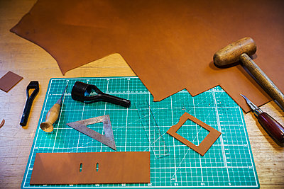 Workbench and cutting mat with a large smooth piece of brown leather, and tools for measuring cutting and stitching, leatherworking  tools.  - p1100m1522552 by Mint Images
