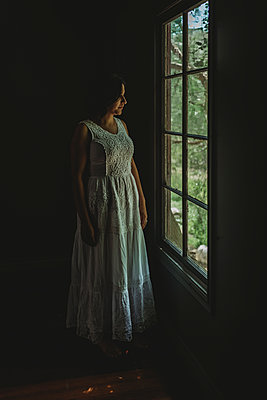 Adult woman in white dress looking out of window in natural light stud - p1166m2130634 by Cavan Images