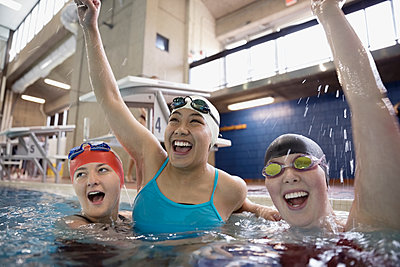 Portrait smiling female swimmers cheering and celebrating in swimming pool - p1192m1447661 by Hero Images